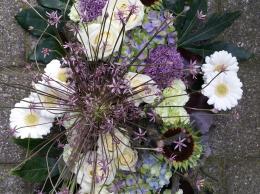 detail rouwbloemstuk met allium en witte rozen
